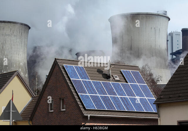 Contrasting sources of energy: a solar electric (pv) generating system on a house roof next to a coal power station, - Stock Image