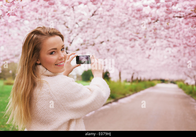 Young woman using her smartphone to capture images of the path and cherry blossoms tree at park, Young female looking - Stock Image