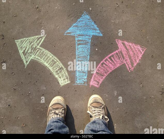 Shoes on the road with arrows - Stock Image