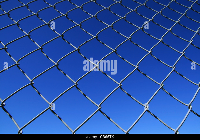 chain link fence mesh with blue sky background - Stock Image