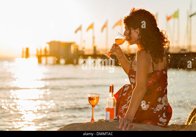 Germany, Bavaria, Nonnenhorn, Woman with wine on the bank of Lake Constance - Stock Image