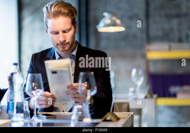 Businessman deciding on what to order in a restaurant - Stock Image
