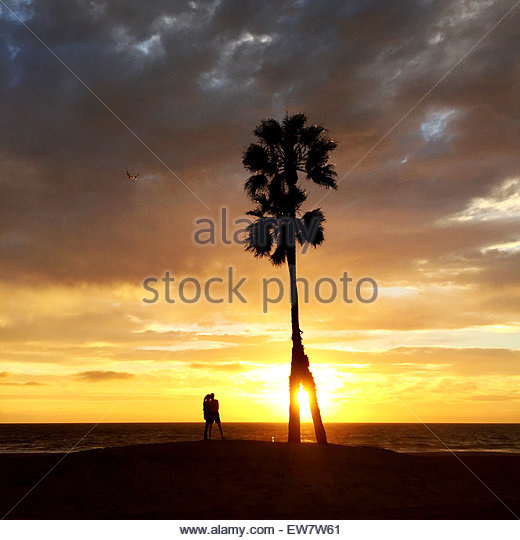 Silhouette of a couple standing on the beach at sunset, Playa del Ray, Los Angeles, LA, California, USA - Stock Image