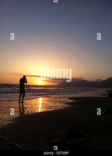 Man photographing the beach at sunset - Stock Image