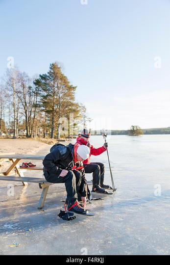 Sweden, Gastrikland, Edsken, Mature woman and man ice skating on frozen lake - Stock Image