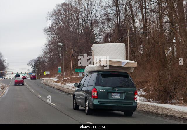 Bed mattresses on top of minivan - USA - Stock Image