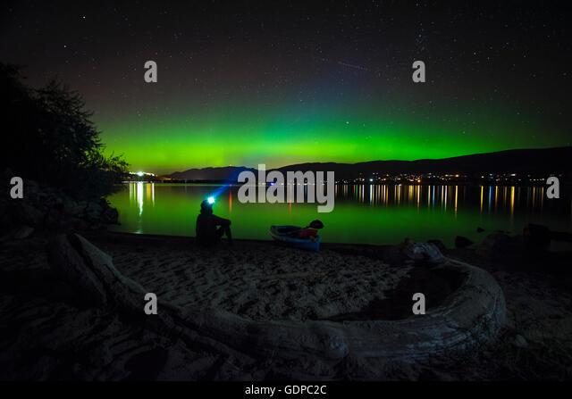 Man looking at aurora borealis over Okanagan Lake, Kickininee Provincial Park, Penticton, British Columbia, Canada - Stock Image