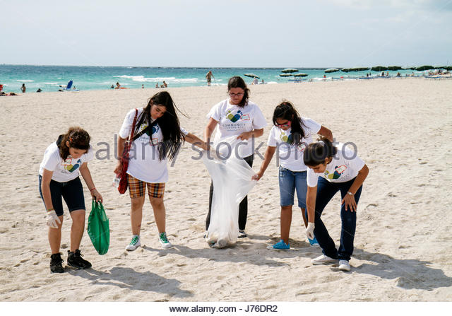 Miami Beach Florida Hands on Miami Beach Clean-up litter trash pollution environment sand volunteer student Hispanic - Stock Image