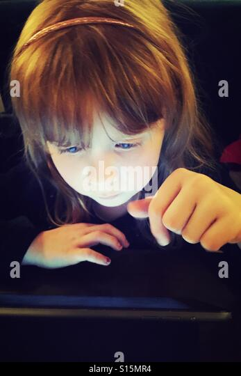 Young girl playing with her iPad Air - Stock-Bilder