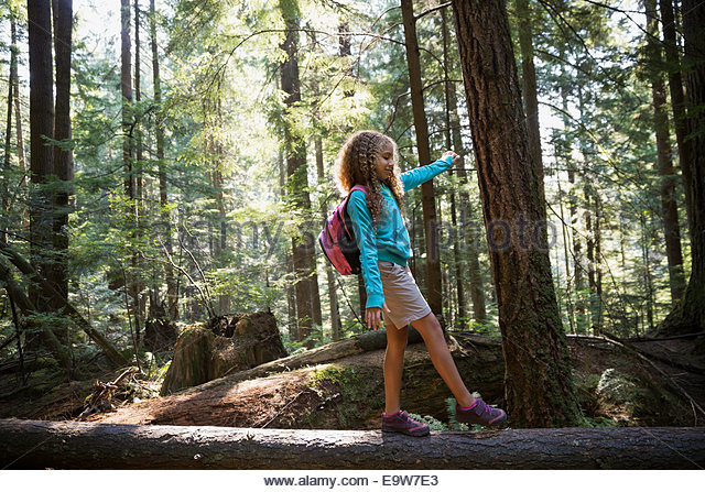 Girl walking on fallen tree in woods - Stock Image