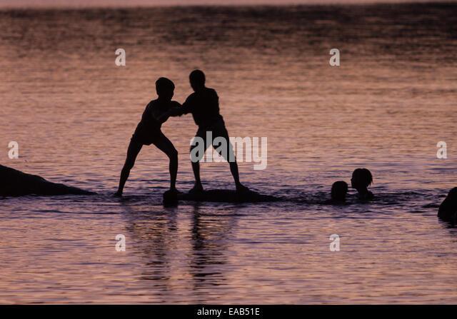 Cambodia.  Angkor Thom.  Boys Wrestling on Edge of Lake. - Stock Image