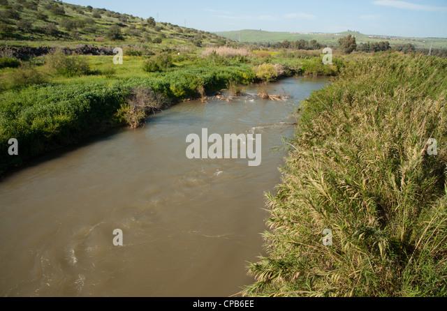 The muddy brown waters of the Jordan River flow toward the Sea of Galilee in northern Israel. - Stock Image