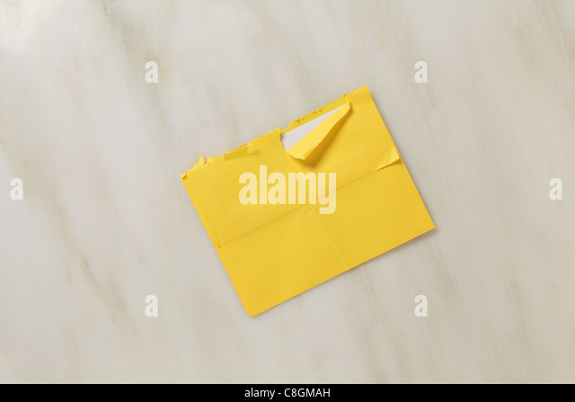A used and slightly torn open postal envelope on a marble surface Bright yellow colored envelope - Stock Image