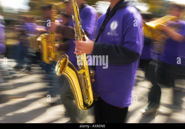 people students marching in parade blowing gold instrument trumpet in purple uniform event celebration music sound - Stock Image