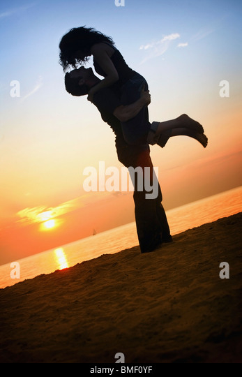 A Man And Woman Together On A Beach In A Sunset - Stock Image