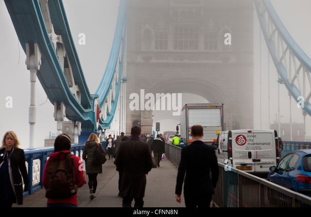 Commuters crossing Tower Bridge through London's smog on a day of record pollution - Stock Image