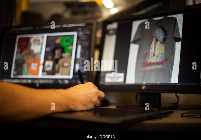 Man using graphic tablet and pen to design t-shirt - Stock-Bilder