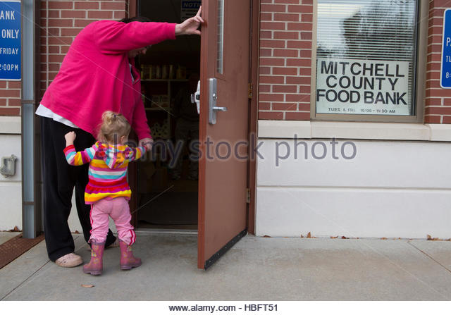 A woman arrives at the Mitchell County Food Bank in Osage, Iowa to receive donated food for her family. - Stock Image