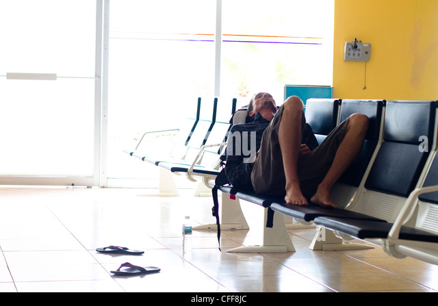 An exhausted male traveler waits in an airport terminal for his flight to arrive at the Manzanillo International - Stock-Bilder