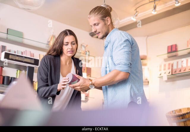 Female worker with colleague discussing while holding product in candy store - Stock Image