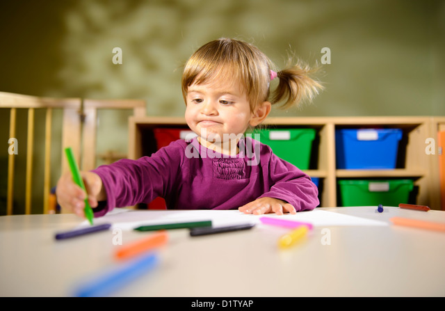 Little girl having fun at school and drawing with colors in kindergarten - Stock Image