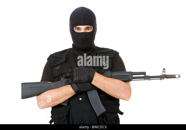 Portrait of violent killer holding firearm and looking at camera with balaclava on his head - Stock Image