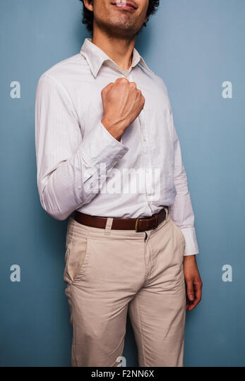Young man standing by a blue wall and fist pumping - Stock Image