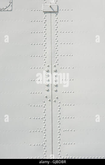 Aluminum fuselage and rivets on old airplane - Stock Image