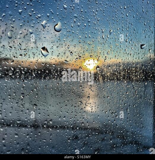 Sun coming up through a curtain of raindrops - Stock Image