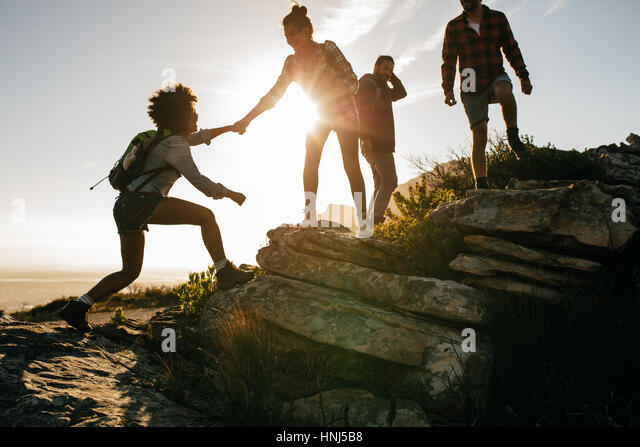 Group of hikers on a mountain. Woman helping her friend to climb a rock. Young people on mountain hike at sunset. - Stock Image