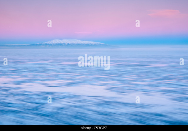 Blurred motion view of outgoing tide and ice at sunrise with Mt. Susitna in the background, Point Woronzof, Anchorage, - Stock Image