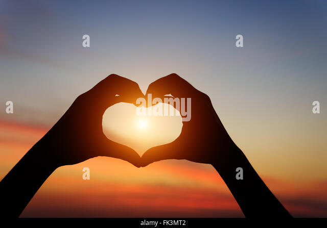 silhouette hand gesture feeling love during sunset - Stock Image