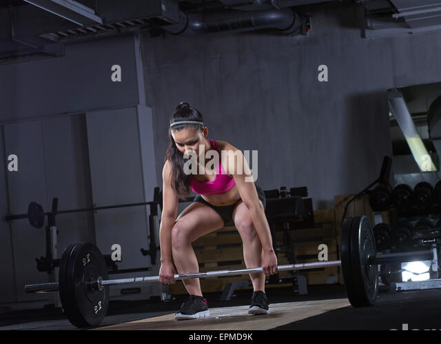 Young woman preparing for weightlifting with barbell - Stock Image
