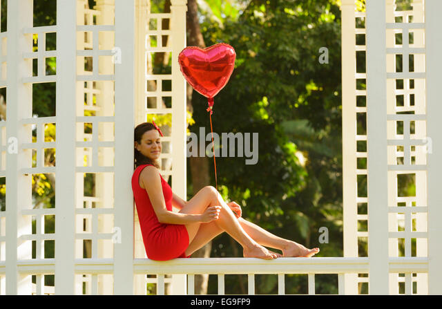 Woman with red heart shape balloon sitting on park bench - Stock Image