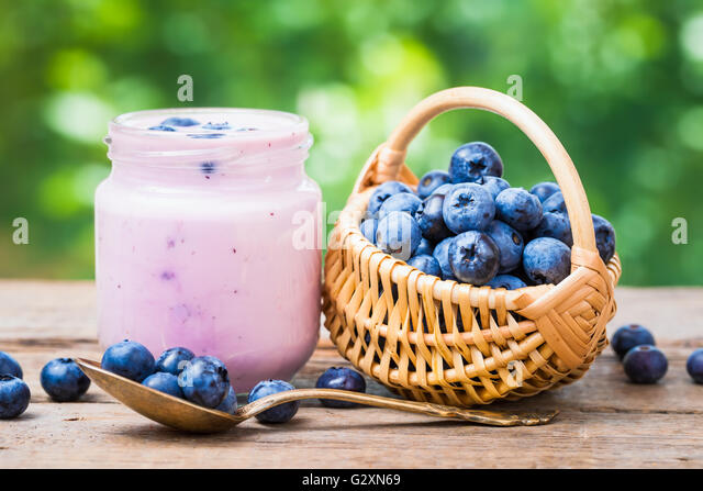 Fresh blueberries yogurt in jar and small basket of bilberries. - Stock Image