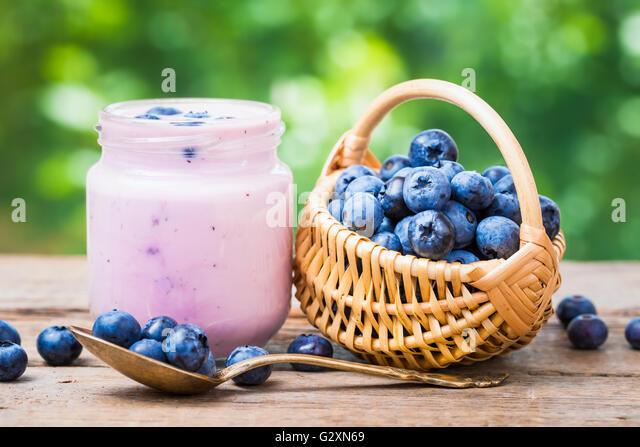 Fresh blueberries yogurt in jar and small basket of bilberries. - Stock Image