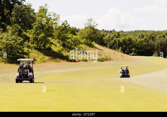 Golf carts on field by trees - Stock-Bilder