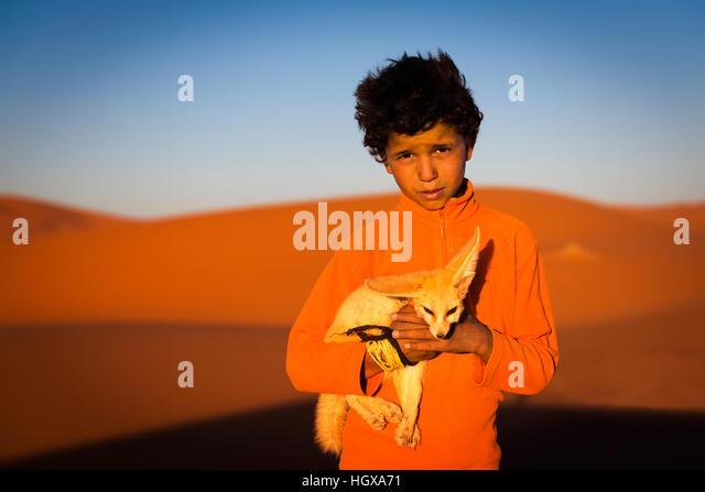 Merzouga, Morocco - April 12, 2016: Berber child holding a desert fox poses in the Erg Chebbi dunes in Morocco. - Stock Image