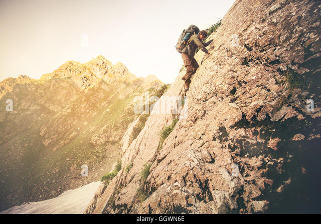 Man Traveler with big backpack climbing on rocks Travel Lifestyle concept mountains landscape on background Summer - Stock Image