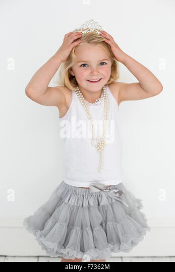 Young girl wearing a tiara and a pearl necklace, posing for a picture in a photographers studio. - Stock Image
