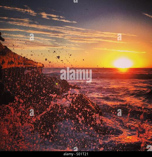 Huge wave crashing onto rocks during sunset. - Stock-Bilder