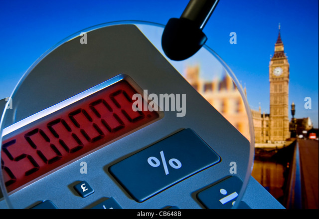 Concept image of calculator 'in the red' with magnifying glass and Houses of Parliament in background Westminster - Stock Image