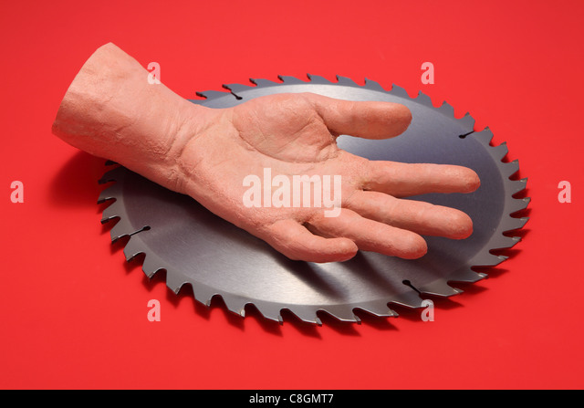 A fake human hand resting in the middle of a metal circular saw blade. Bright red background - Stock Image