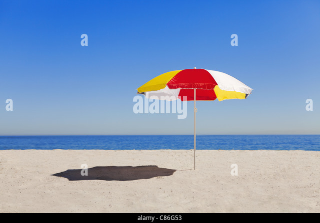 Umbrella in sand on empty beach - Stock Image