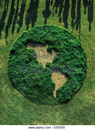 Green grass circle 25 ft diameter seen from overhead with long human shadows late afternoon warm yellow light - Stock Image