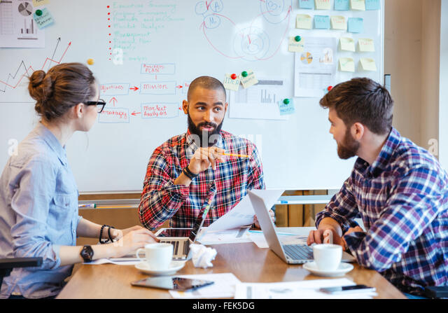 Group of creative young people making new project together in conference room - Stock Image