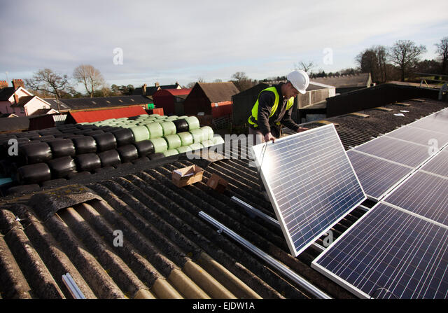 Jake Beautyman installs solar panels on a barn roof on Grange farm, near Balcombe. The installation is part of an - Stock-Bilder