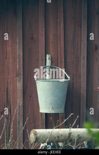 Old bucket hanging on wall of rural building. Vintage farm equipment. - Stock-Bilder