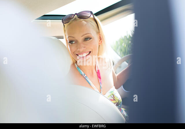 Happy beautiful woman looking back while driving car - Stock Image