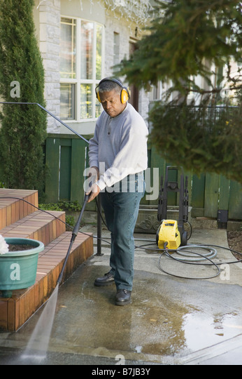African American man using a power washer, Vancouver, BC - Stock Image